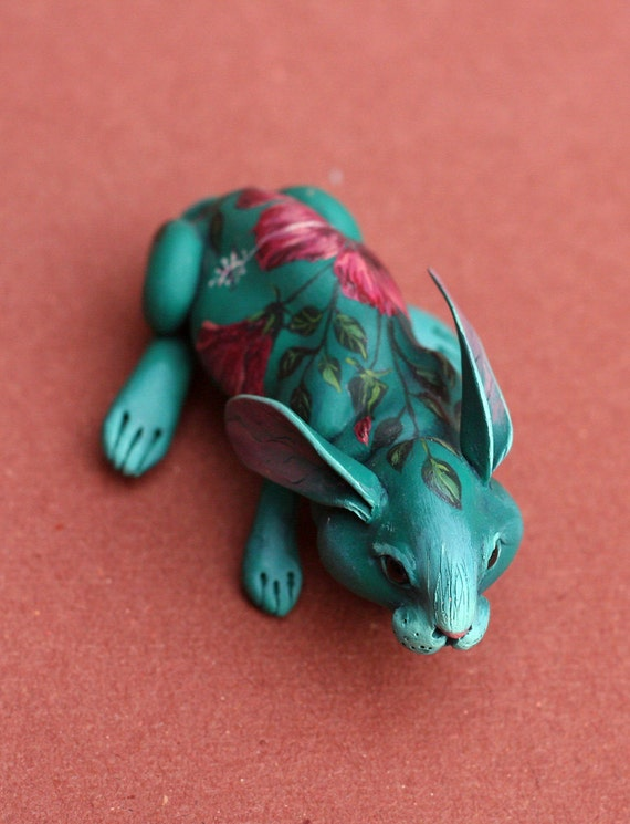 Aquamarine rabbit with dark hibiscus on the back. Polymer clay hand painted miniature by Madre Olius