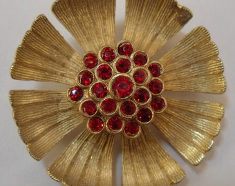 Gold tone flower brooch with deep red rhinestones