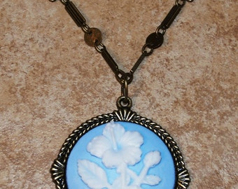 Bronze tone antique style 24 inch necklace with blue brooch pendant accented with white flower