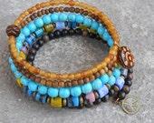 Boho chic - multicolored glass, bone, wood, and genuine ebony, hand painted bead charm, and a peace sign beaded bangle