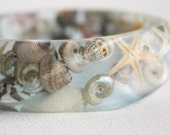 seashell swirl eco resin bangle with shells and starfish in transparent blue