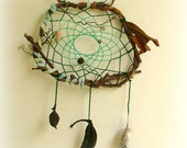 Baby mobile earth art magical dream catcher weaved in 2 shades of green with black pods and spotted feathers.
