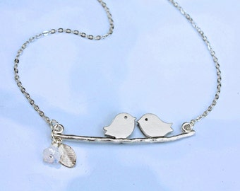 love birds necklace in silver. Sparrows kissing on leafy branch with flower
