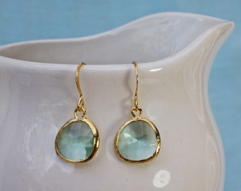 Aqua blue earrings with gold bezel setting. Framed and faceted