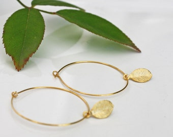 Delicate gold hoop earrings with tiny gold leaf
