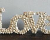 "Seashell encrusted ""LOVE"" sign"