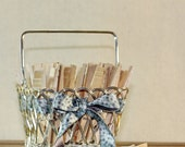Vintage wooden clothespins in a silver strawberry basket