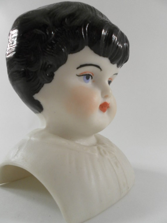 Vintage Sweet painted porcelian  china doll head with black hair and pretty blue eyes
