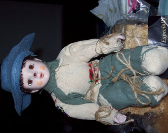 Little boy sitting on a hay stack porcelain doll