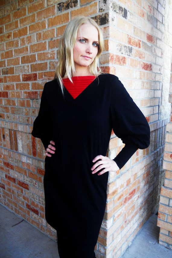 Black sweater dress with red accordian detailing and puffy sleeves size small