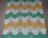 Cream, green, and yellow, striped baby blanket.