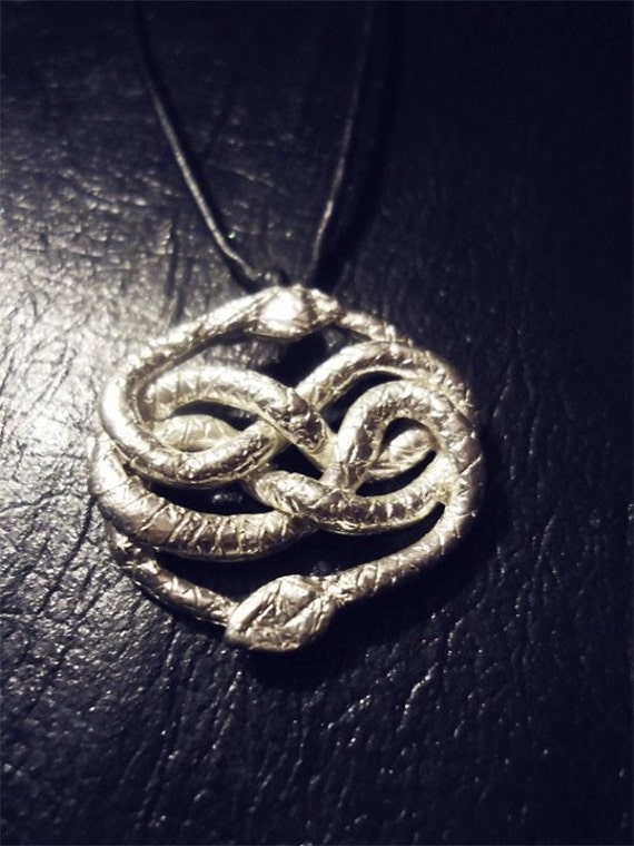 silver necklace charm inspired by auryn from the neverending