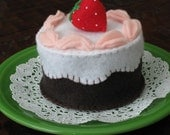 Chocolate felt cake with vanilla frosting and a strawberry