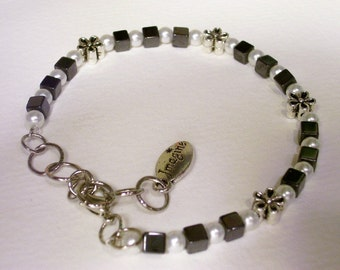 Magnetic bracelet with white pearls, black magnetic beads, and flower beads