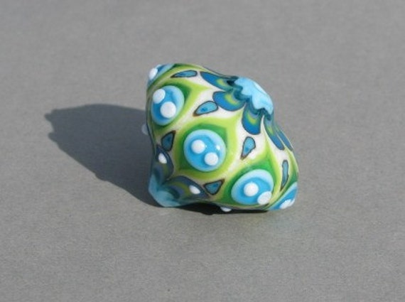 Handmade lampwork glass bead in different shades of green, blue and white by Flamejewels.