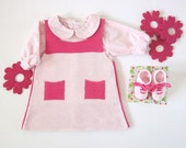 A sweet  knitted baby dress with little pockets in pink and fuchsia