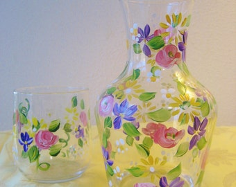 Hand painted bedside carafe with rose pattern and violets, pattern the same but new design has a ribbed base