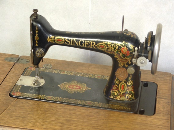 Vintage 1910 era Singer treadle sewing machine with attachments, extras, original manual