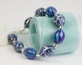 Purple, turquoise, black and white oval beaded bracelet