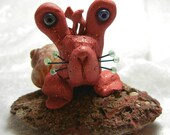 Polymer clay sculpture - Curious red snail with big blue eyes on lava burp