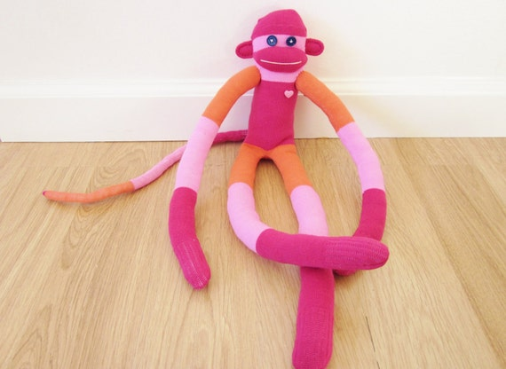 Knee sock monkey plush doll with color blocked magenta, pink, and orange stripes