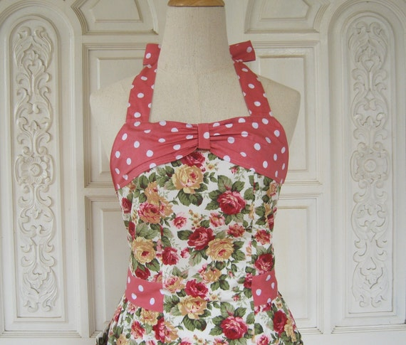 Retro apron with bow, red and yellow rose pattern on white fabric, with white dots on a pink background, fully lined.