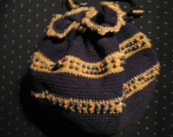 Navy blue knitted drawstring bag with gold bands embedded with beads