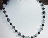 A quartz with black tourmaline needles necklace, with onyx beads and silver filigree.