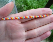 Red, blue and yellow woven friendship bracelet.