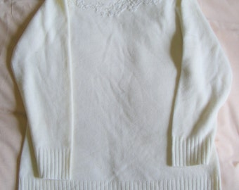 Ladies cream sweater with beaded detail.