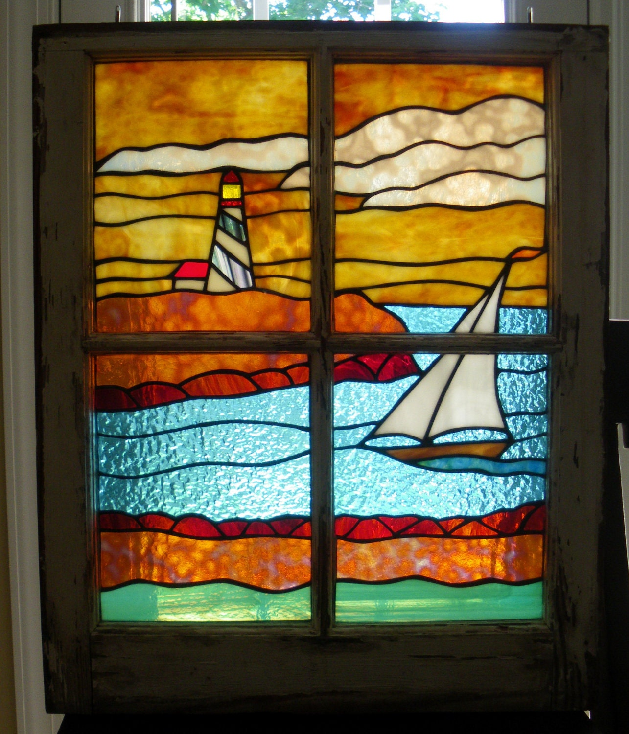 stained glass sailboat panel in window frame