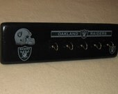 "Oakland Raiders key rack (black)  (50% off with purchase of any  ""sports series coat rack"") at regular price."