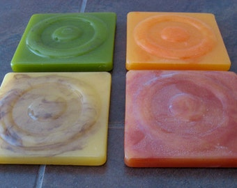 Four thick colorful lucite coasters