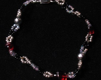 Red and Silver beaded Bracelet with glass seed beads and glass larger beads and a silver plated jump ring and lobster clasp.