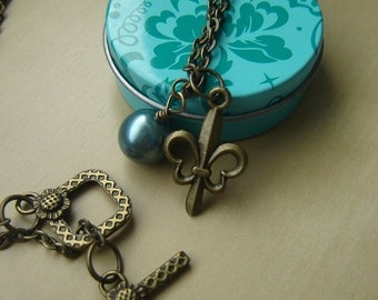 Antique brass fleur-de-lis necklace with aqua pearl