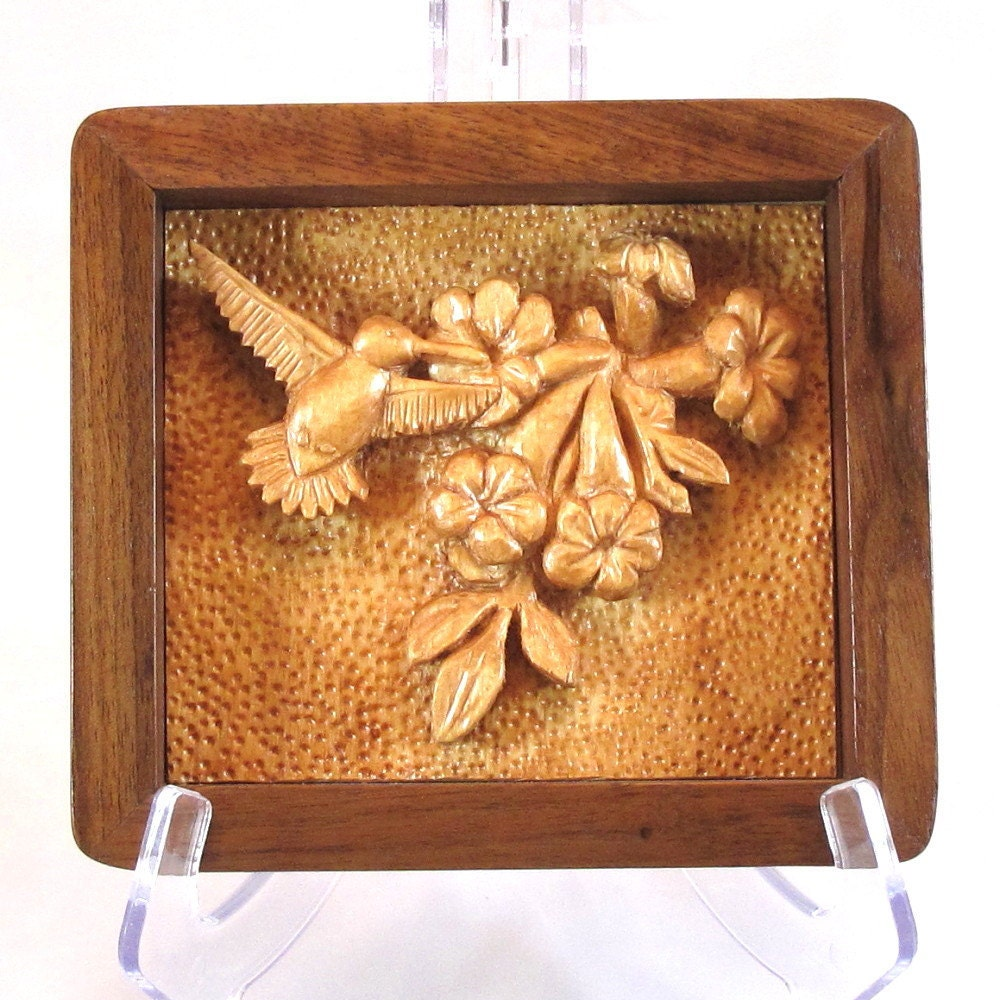 Relief carving of a hummingbird with flowers handmade