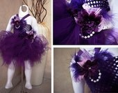 Purple knee length tutu dress. Crocheted purple top with flower, feather, and bead embellishments.Can be made for 6mths -4T. Prices Vary