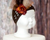 Brown kufi hat with rust hydrangea and feather, tulle and rhinestone embellishments. Great for Fall