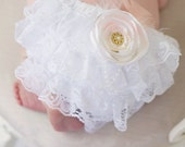 White lace diaper cover bloomer and contains flower, lace, bead, and feather embellishments.