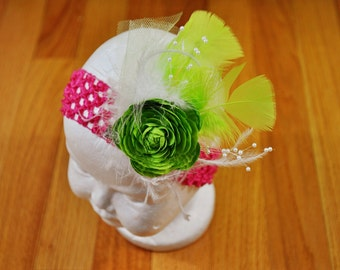 Exquisite pink headband withgreen flower, feather and embellishments.