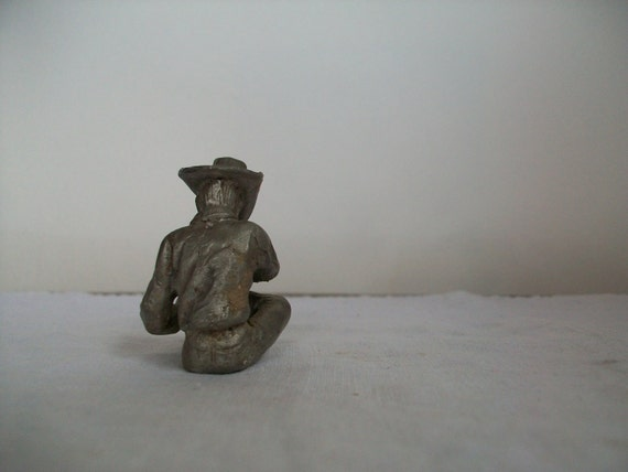 small tired cowboy pulling off his boots . cowboys . cowboy figurine . country western