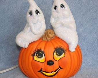 Ceramic lighted Jack O Lantern with two white sparkling Ghost lovers sitting on on top