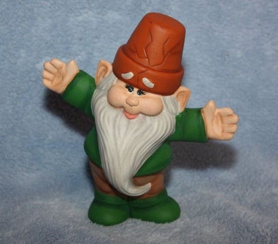 Handpainted Ceramic Mini Crackpot Gnome dressed in green with his arms stretched.