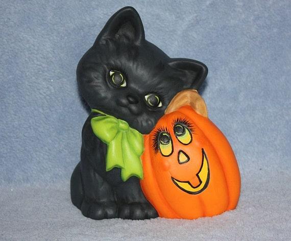 Little Black Kitten Leaning on a Pumpkin