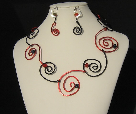 Handmade funky, yet elegant red and black metal spirals accented with red and black crystals.