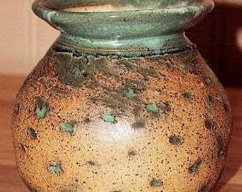 Pottery vase with intricate design and green rim