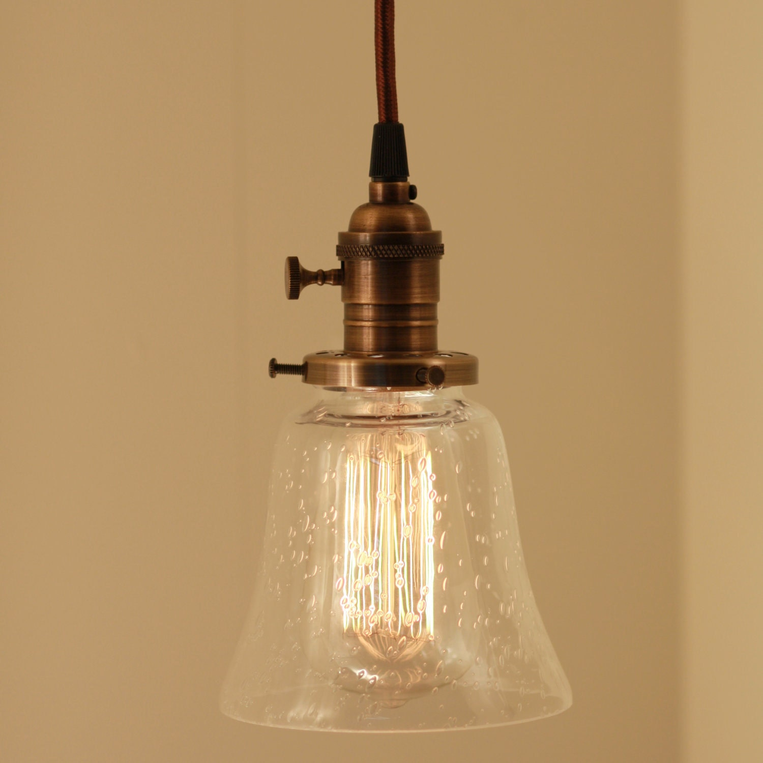 A Pair Of Pendant Light Fixtures With Seeded Clear Glass