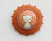 Brown felt brooch with white bear