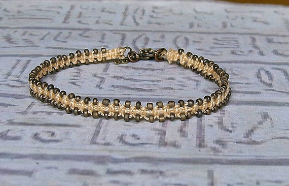 Macrame friendship bracelet in peach and bronze.