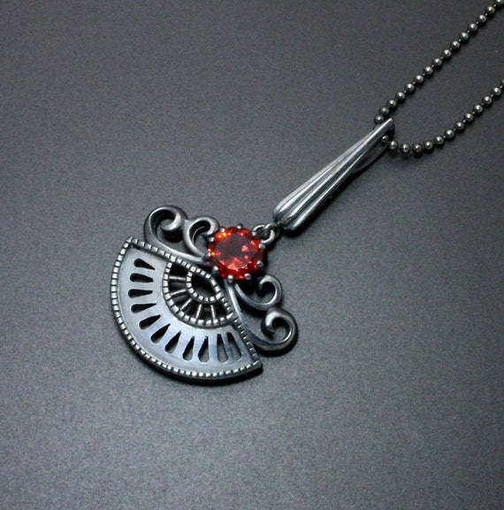 Goth style pendant with a red garnet